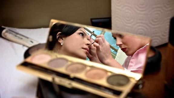 bride's makeup stylist in cosmetic mirror