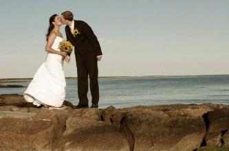 Bridal ouple kissing at beach